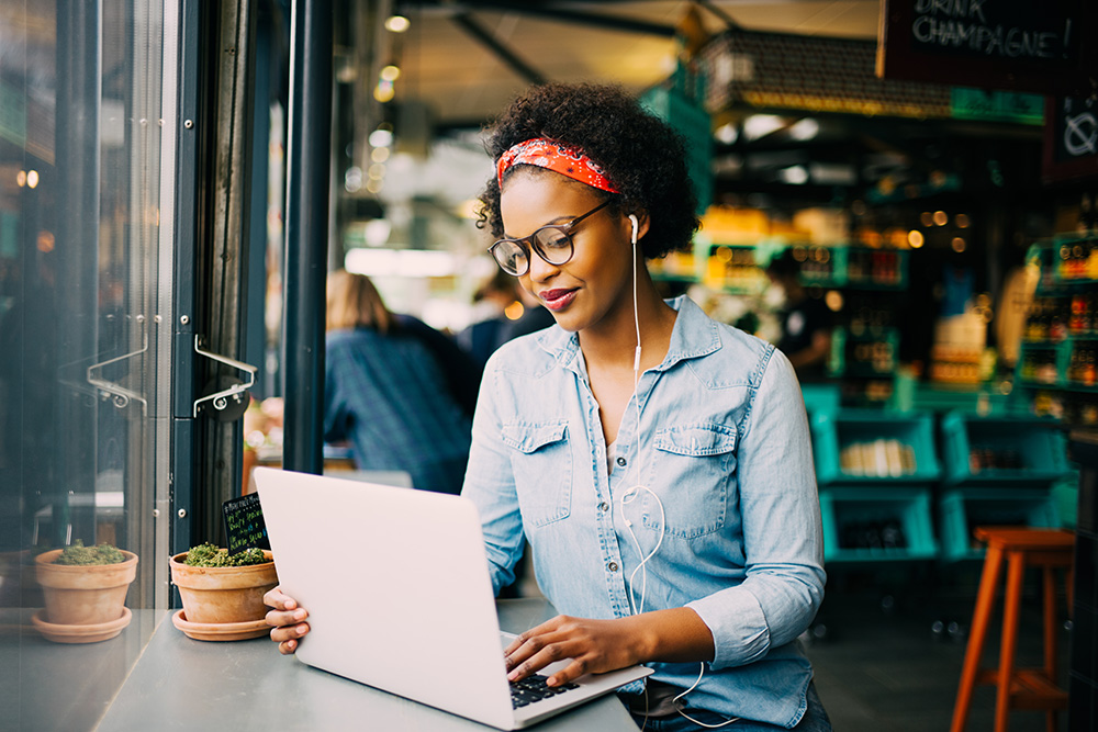 African American woman with glasses writing on a laptop in a cafe